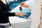 picture of car keys  - cropped view of man in car dealership giving car keys to client - JPG
