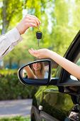 foto of car key  - close up of female with arm outstretched taking car keys from man - JPG