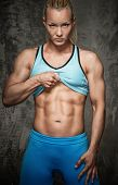 Attractive bodybuilder girl showing her abdominal muscles