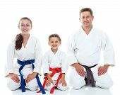stock photo of karate  - Dad with two daughters sitting in a ritual pose Karate - JPG