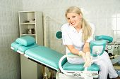 stock photo of gynecological exam  - beautiful young doctor sitting on the gynecological chair in her office - JPG