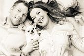 stock photo of dog eye  - Lovely attractive couple and dog together studio shot white background - JPG
