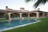 pic of hacienda  - Swimming pool and lawn in front of spacious house against clear sky - JPG