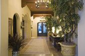 stock photo of hacienda  - Lit chandeliers at entrance hallway along potted plants in modern house - JPG