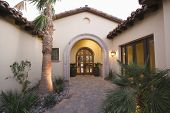 picture of hacienda  - Paving path along plants leading to closed doors of modern house - JPG