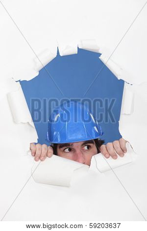 Tradesman peeking out through an opening in a wall