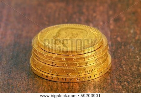 Golden old coins stack. Russian and swiss gold. Focus on nearest edge,