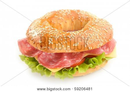Bagel sandwich with sausage, cheese, and lettuce isolated on white background