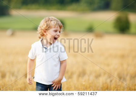 Little Boy Of Three Years Having Fun On Yellow Hay Field