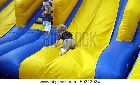 children playing on inflatable slide