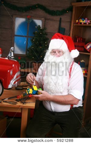 Santa Claus paints a toy for christmas