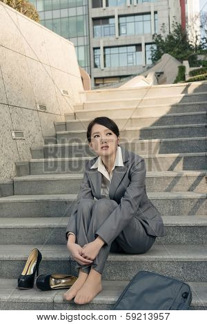 Sad business woman feel helpless and sit on stairs in modern city.