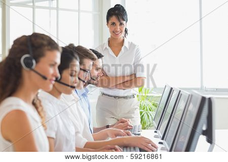 Portrait of happy female manager with business staff working in a call center