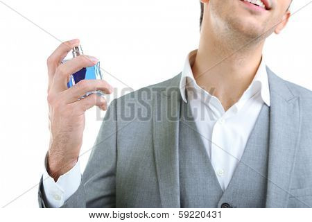Handsome young man using perfume isolated on white