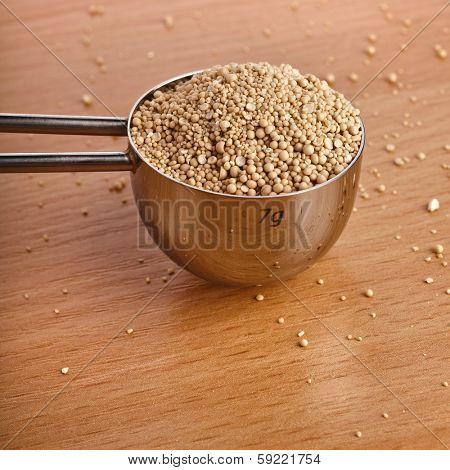 Dry yeast heap in metal scoop on wooden board table