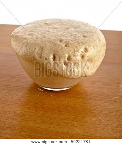 Rising Yeast Dough in glass bowl on wooden table  Isolated on White Background