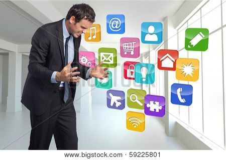 Stressed businessman gesturing against computing application icons