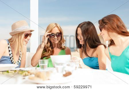 summer holidays, vacation, internet and technology concept - smiling girls looking at tablet pc in cafe