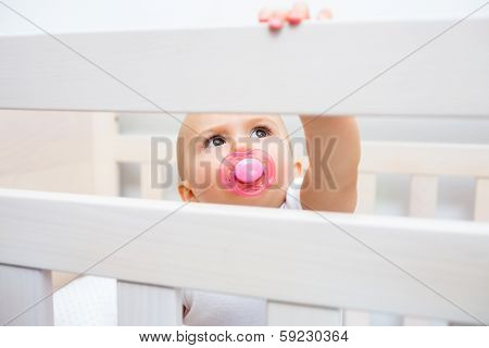 Closeup portrait of a cute baby with pacifier in mouth in the crib at home