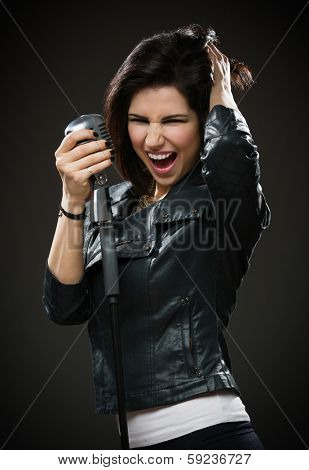 Half-length portrait of female rock musician wearing black jacket and handing microphone on grey background. Concept of music and rave