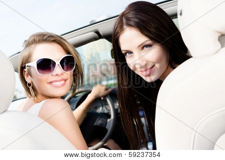 Two girls ride the car. Teenagers have a little trip on vacation
