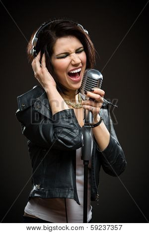 Half-length portrait of female rock singer with microphone and earphones. Concept of rock music and rave
