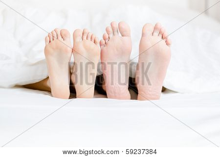 Close up of two pairs of feet of the couple next to each other in bedroom
