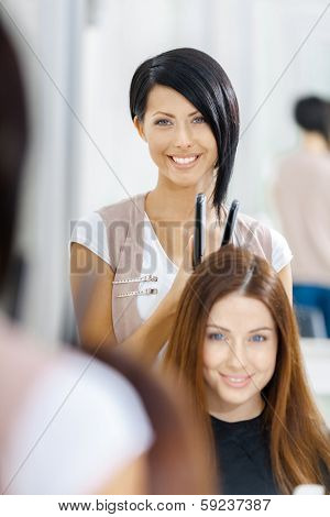 Reflection of hair stylist doing hair style for woman in hairdressing salon. Concept of fashion and beauty