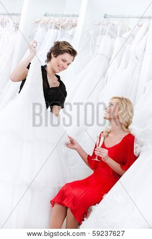 Shop assistant suggests another dress to the bride while she is drinking champagne