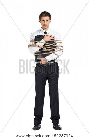Full-length portrait of businessman handing briefcase who tied with the cord, isolated on white. Concept of slavery and violence
