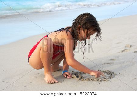 Beautiful Girl Writing In The Sand