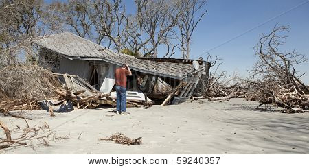 man grieving over flood destroyed house