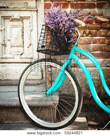 Vintage Bycycle With Basket With Lavender Flowers Near The Wooden Door
