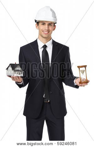 Real estate agent wearing white hard hat hands model house and hourglass, isolated on white