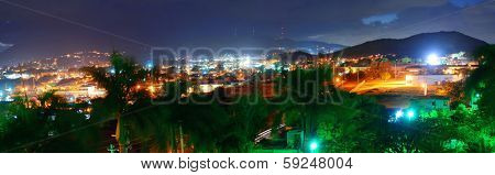 Vacation resort over mountain at night with lights in San Juan, Puerto Rico.
