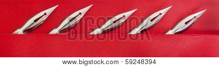 Metal pen nibs used for pen and ink drawing on a red satin background.