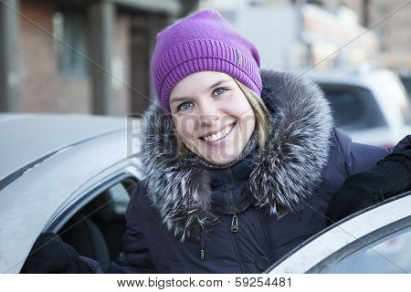 Happy Pretty Woman With An Open Car Door In Winter Clothes