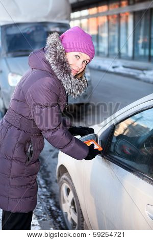 Woman At Winter Cleaning Car Windows And Mirrors Before The Trip