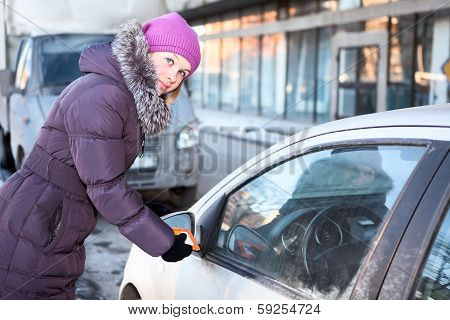 Woman In Winter Clothes Cleaning Car Windows And Mirrors Before The Trip