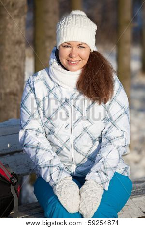 Woman Portrait In Winter Hat And Mittens Sitting On Bench