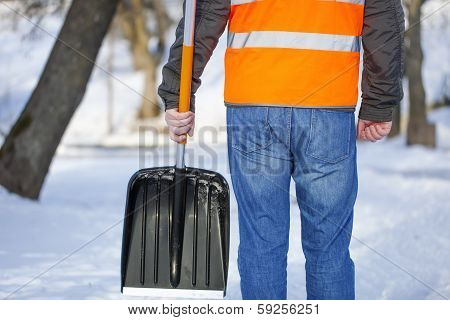 Man with a snow shovel on the sidewalk in winter