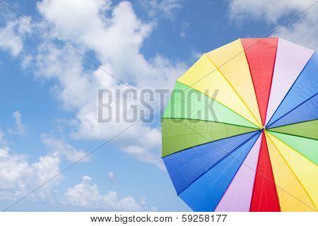 Rainbow umbrella against cloudy sky