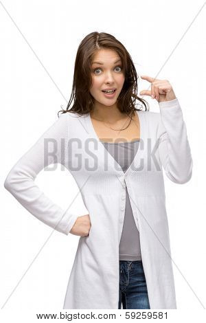 Half-length portrait of amazed woman showing small amount of something, isolated on white
