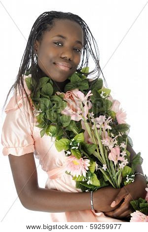 A beautiful tween girl adorning herself with leaves and flowers.  On a white background.
