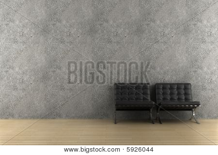two black armchairs in front of gray wall