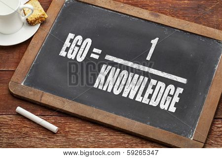ego and knowledge concept (illustration of Albert Einstein words) on a  vintage slate blackboard with a chalk and  cup of coffee