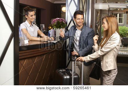 Young couple upon arrival at hotel reception.