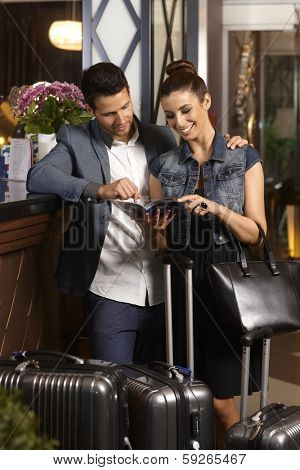 Happy young couple looking at sightseeing catalogue upon arrival at hotel lobby, surrounded by suitcases.