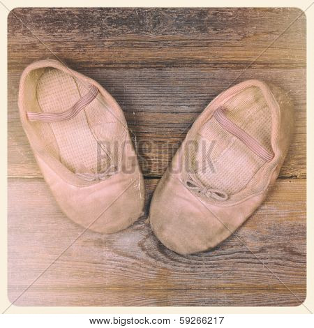 A pair of tiny ballet shoes on old wood floor, with nostalgic feel suitable for mother's day or grandparents day. Filtered to look like an aged instant photo.
