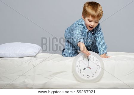 Little boy in blue pyjamas with clock